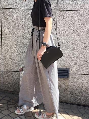 黒Tシャツにグレーのハイウエストワイドパンツを合わせたコーディネート。ジャストサイズのトップスをインして、すっきりメリハリを効かせています。メタリックなスポーツサンダルで、都会的な雰囲気をプラスして。