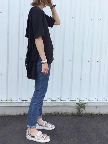 5分袖のゆったりとした黒Tシャツに、タイトなブルージーンズを合わせてすっきりと。さらに、爽やかな白のスポーツサンダルで足元に軽さを与えています。