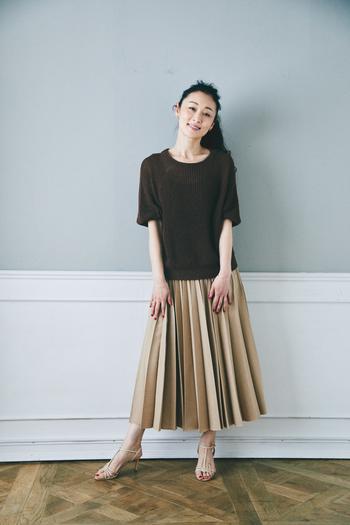 ハリのある生地のプリーツで陰影が美しいスカートに、最近楽しめるようになったというヒールの靴を合わせた上品な着こなし。シンプルなコーディネートに、華奢なネックレスを2点つけてさりげないアクセントに。  プルオーバーセーター、プリーツスカート/クロス&クロス