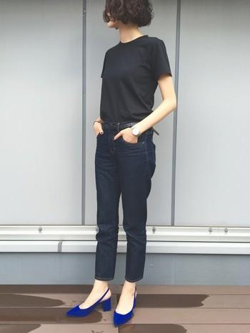 首元がやや詰まった黒のクルーネックTシャツに、濃いめのデニムを合わせたシンプルコーデ。鮮やかな青のパンプスでクールで女性らしいアクセントをプラスしています。