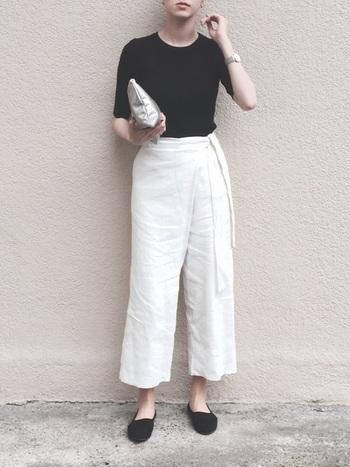 程よくフィット感のある黒Tシャツをラップシルエットの白パンツにインした女性らしいきれいめコーデ。黒のフラットサンダルで程よくカジュアルダウンして、抜け感をプラスしています。