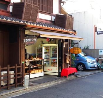 70年の歴史を持つ老舗パン屋さん「まるき製パン所」。外観は京都らしい町家の店舗で風情があります。 丸い木の看板も柔らかい雰囲気で迎えてくれます。6:30~オープンしている早起きパン屋さんです。