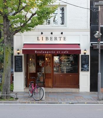 地下鉄京都市役所前から徒歩5分ほどのBoulangerie de la Liberte'(ブーランジェリエ デ ラ リベルテ)は、大きなガラスがはめ込まれた木製の扉が特徴的で、まるでパリの街角を思わせるようなお洒落なお店です。お店の2Fはカフェになっていて、朝早くから開いているパリのカフェのように、何時に来てもお気に入りが食べられる幸せがここにはあります。