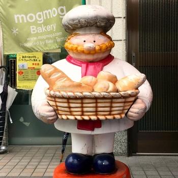 可愛い看板人形が出迎えてくれる「モグモグベーカリー」は地元の人に愛され続ける昔ながらのパン屋さんです。 そして「たま木亭」のオーナーのお父さまが営むお店でもあります。