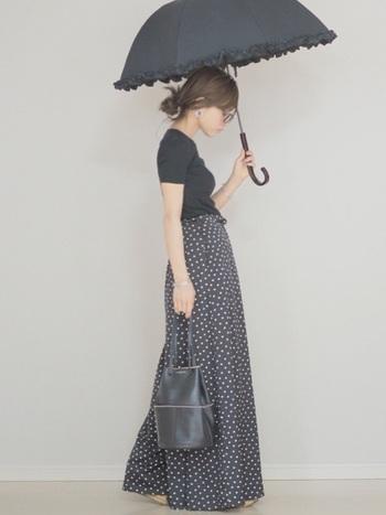 タイトな黒Tシャツにドッド柄のワイドフレアパンツを合わせた大人上品なワントーンコーデ。小ぶりなバケツバッグや日傘などレディな小物を上手に組み合わせています。