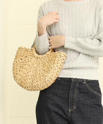 きゅっと編み込まれた半円型のかごバッグ。ちょっぴり個性的な形が可愛らしいですね。たっぷり荷物が入り、中布がついているので、バッグの中も見えません。