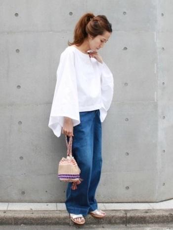 白いたっぷりとしたブラウスにデニムを合わせたシンプルな着こなしに、きんちゃくかごバッグがとても可愛らしいアクセントに。サンダルに合わせて、とても涼し気で爽やかな印象です。