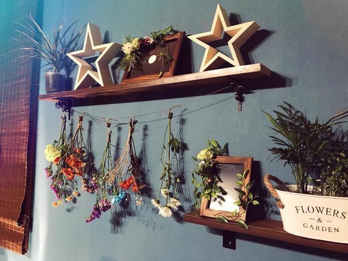 壁に取り付けられた小さなウォールラック。お気に入りの雑貨をディスプレイする場所に、ドライフラワーも一緒に吊るして華やかさをプラス。プランターの観葉植物ともマッチしていますね。