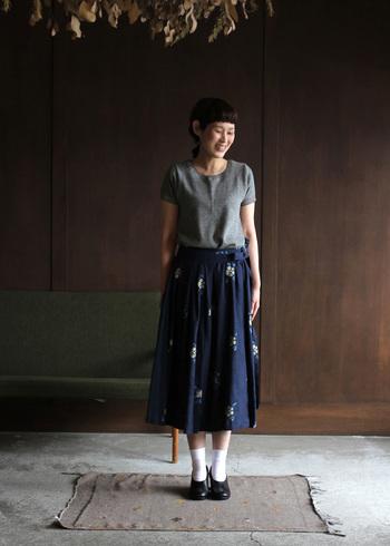 お気に入りの柄スカートを主役にしたいなら、ウエストまで見せてコーディネートするのがコツ。フェミニンな花の刺繍に、敢えてカジュアルなTシャツのようなニットを合わせたところがこなれています。