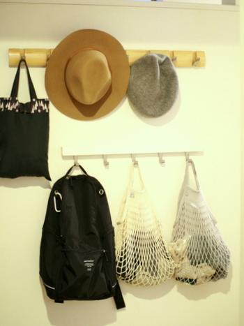 玄関の壁にフックを取りつけて、リュックや帽子の一時置きの場所を作ってみましょう。これなら、帰宅後すぐに掛けられて、出かける際もサッと必要なアイテムを身につけられます。また、手袋やマフラーなどの直接掛けられない小物類は、ネットバッグを活用すると◎