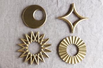 銅と亜鉛の合金である真鍮は、表面の細かな粒子が散りばめられたような質感がぬくもりを感じさせ、カトラリーや生活雑貨としても人気があります。そんな真鍮から作られたFUTAGAMIの鍋敷きは、画像左上の「月」、右上の「星」、左下の「銀河」、右下の「太陽」の4種類で、大きさもそれぞれ違います。