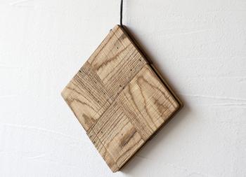 そしてこちらの、富山県産の虫喰いのナラを使った鍋敷き「チェック」は、4通りの使い方ができる優れたアイテムとなっています。まずは「大きめの鍋敷き」としてそのまま食卓で使用したり、革紐で吊り下げてナチュラルな「インテリア」にも◎。