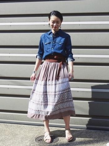 幾何学模様の刺繍がエスニックな雰囲気を醸し出すフレアスカート。コンパクトなデニムシャツをインしたナチュラル&カジュアルなスタイリングが素敵。革のサッシュベルトがトップスとボトムスの良い繋ぎ役になっています。