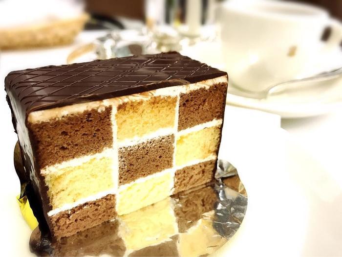 断面の美しさに惹かれる「モザイクケーキ」は、ココアスポンジとバタースポンジをブロック状に組み合わせたケーキ。創業当初から作られている数少ない定番ケーキのひとつなんですよ。創業当時は4分割だったのが、現在は9分割に。食べるのがもったいないぐらい繊細なデザインです。