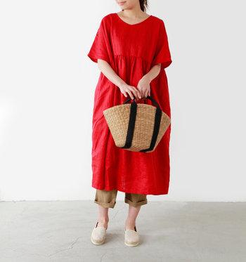 赤のリネンワンピースに、トート型のカゴバッグを合わせた夏らしい着こなし。バッグの色と合わせたベージュのパンツは、少し折り返して脚を見せることで女性らしさをアピール。