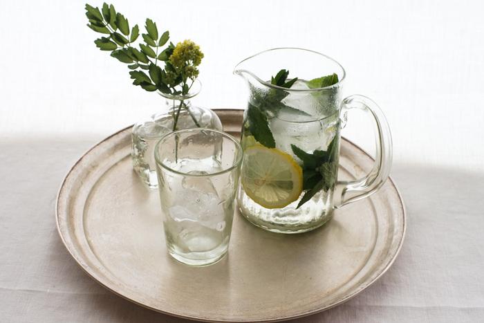 ガラス工房「橙」の吹きガラス作品。ほんのり緑がかったくるみガラスでできていて、自然光と溶け込み独特の優しい雰囲気。ピッチャーは持つのにちょうどいい大きさで、冷たい水にミントとレモンを入れただけでも美しく、おもてなしにぴったり。タンブラーとペアで使えばさらに素敵です。