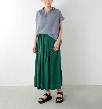 ユーズド感のあるダンガリー生地のスキッパーシャツに、鮮やかなグリーンのロングスカートを合わせたリラックススタイル。シャツをフロントインすることでこなれた印象に見せています。