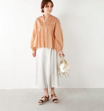 ふんわりとしたギャザースキッパーシャツに、スカートのようなワイド幅のガウチョパンツを合わせた大人のリラックスコーディネート。淡いオレンジ色とホワイトカラーの組み合わせが優しい雰囲気です。シンプルなスタイリングは、フリンジバッグやカラフルメッシュのサンダルで遊び心を加えて。