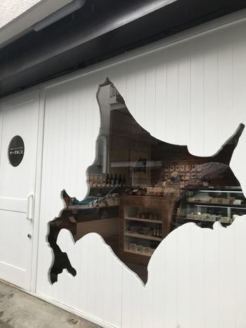 """清澄白河の駅から5分ほど歩いた住宅街にある「チーズのこえ」は、北海道の形にくり抜かれた白壁が個性的な外観が目印。店名の由来は、""""チーズは喋ることができない。コンシェルジュだけがチーズの声を聴くことができる""""という想いからつけられました。オーナーであるチーズコンシェルジュのチーズの知識の深さが表れているよう。"""