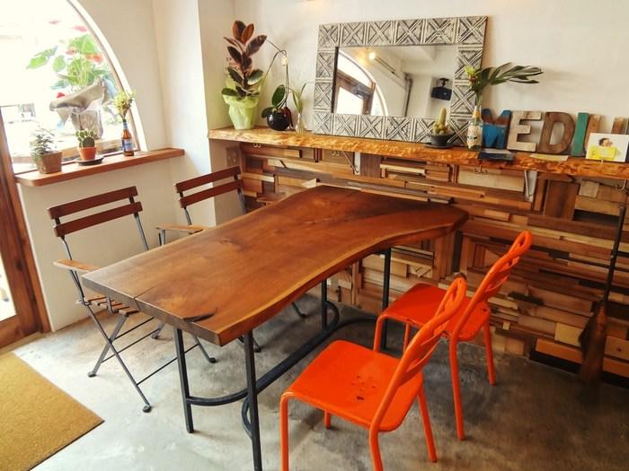 カウンターとテーブル12席が中心の店内。木を多く使ったナチュラルな雰囲気の中に、オレンジやグリーンをアクセントカラーがおしゃれです。
