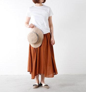 シンプルな白Tシャツにテラコッタカラーのアシンメトリーロングスカートを合わせた涼しげなサマースタイル。上下無地のシンプルコーデには、マルチカラーのエスパドリーユで遊びとニュアンスを加えてみるのもおすすめです。
