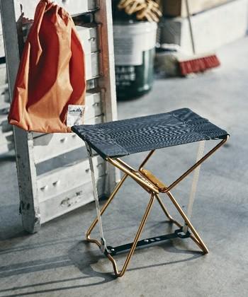 ゴールドのフレームがおしゃれなマイクロチェア。重さ約500gの軽量なアルミフレームで作られた折りたたみ椅子です。