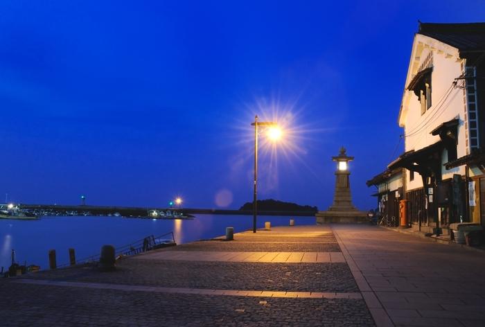 「常夜燈」は今でいう灯台で、安政6年、江戸時代末期に建てられました。石で作られ高さ5.5mの常夜燈は、蒸気機関による船が少なかった時代に、明かりをともして港の場所を知らせました。今でも鞆の浦のランドマークになっていますね。 「雁木」とは、階段状の港のことで、常夜燈の手前左側が階段状になっています。潮の満ち引きによって船がつけられる高さを変えられるため、潮の状況に合わせて荷物を運ぶことが苦労なく行えるそうですよ。