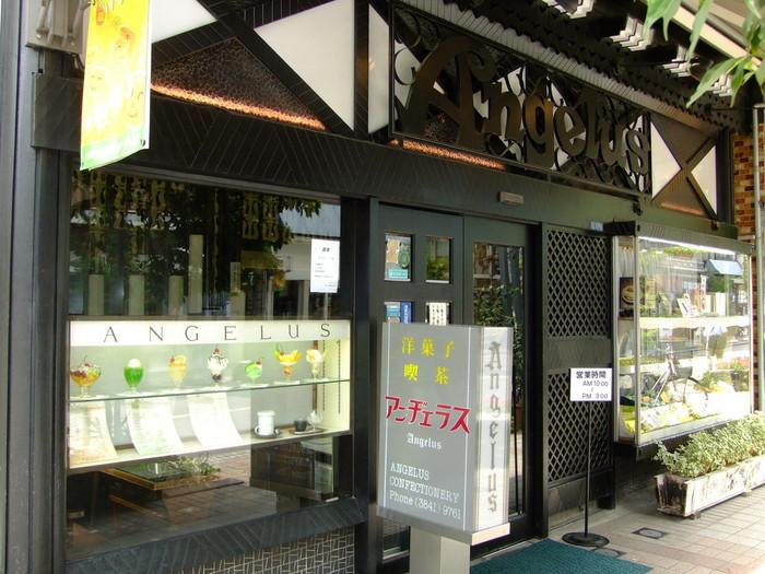 """東武伊勢崎線の浅草駅から徒歩5分ほど、オレンジ通り沿いにある「アンヂェラス」。レトロな外観が下町の街並みにしっくりと馴染んでいます。昭和21年(1946年)から続く老舗の喫茶店で、戦後間もない頃に""""甘いものをみんなで食べてほしい""""という想いから、現オーナーの祖父母が始めたそうです。"""