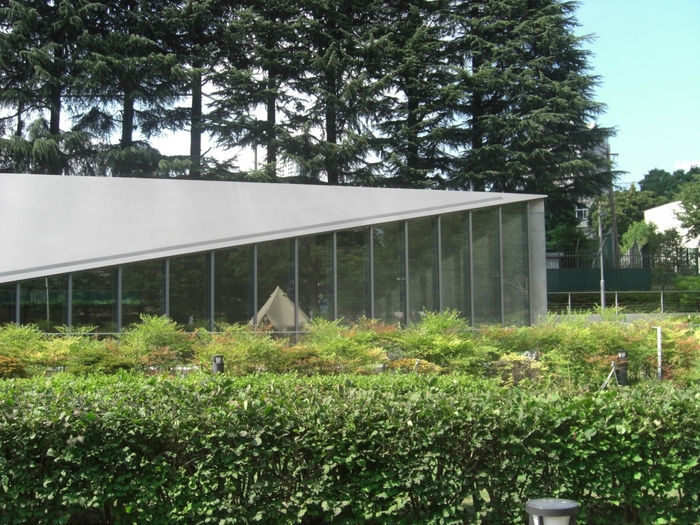 """六本木にある「21_21 DESIGN SIGHT」は、東京ミッドタウン内の緑が多く静かな場所にあります。設計を手がけたのは建築家の安藤忠雄氏。三宅一生氏の服づくりのコンセプト""""一枚の布""""に着目し、一枚の鉄板を折り曲げたような屋根を考案したそう。"""
