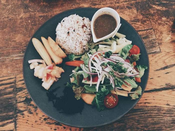 お店の看板メニュー、旬野菜のランチプレート。贅沢に25種類の野菜が食べられるので、日頃の野菜不足が気になる方にもおすすめ。ドレッシングはゴマと柚子の2種類から選べるのでお好みのものをチョイスして。