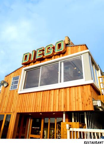 江ノ島の手前、洲鼻広場近くの「ディエゴ・バイ・ザ・リバー」は江ノ島を代表するカフェレストラン。2F建てのアメリカンな建物はサーフボードの保管庫も兼ねているそうで、ボードがずらりと並んでいて江ノ島らしい雰囲気を存分に味わえます。