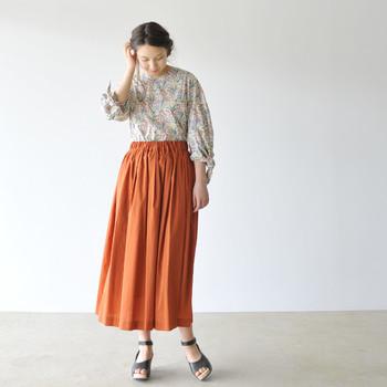 動くたびにドレープが揺れ、エレガントに着こなせるスカートです。花柄ブラウスと合わせた、クラシカルなコーディネートがよく合っています。