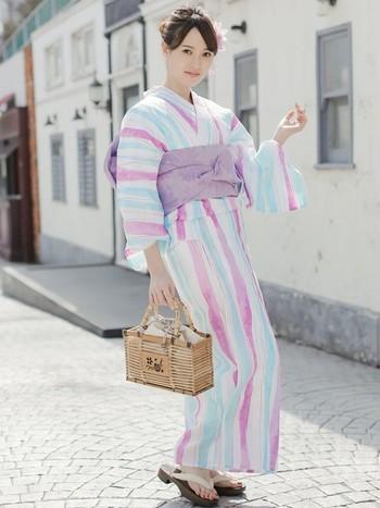 爽やかな水色も入ったピンクストライプ。同じ温度感を持つ淡色の帯を結んで、更に涼やかに。バッグと下駄で落ち着いた雰囲気を取り入れることも忘れずに。