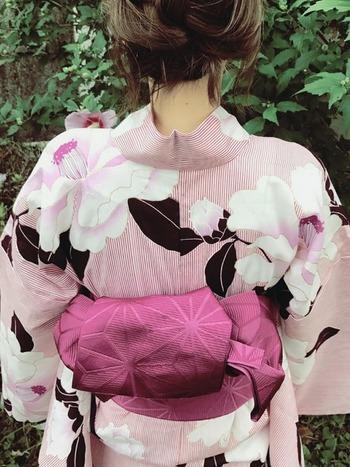 大きな花柄の浴衣は、シックな雰囲気にまとめて。ピンクで女子感を演出しながら、浴衣の葉柄の黒、帯の渋みある色味が大人っぽさを格上げしてくれます。