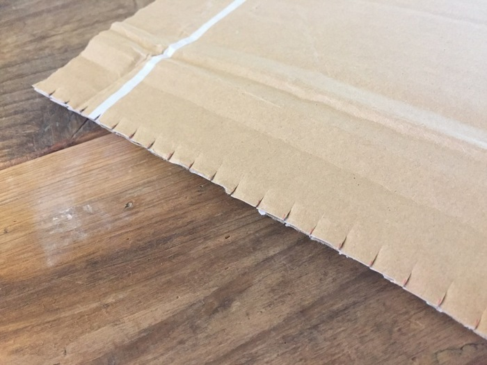 ウィービングを作るには織り機が必要ですが、身近な段ボールでも代用することができます。左右同じ位置になるように1cm間隔で切りこみを入れたら、段ボール織り機の完成です。