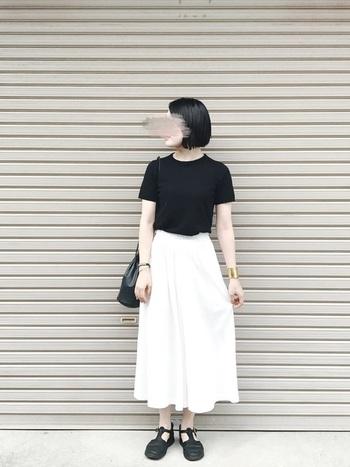 白のスカートに、黒のトップスを小物を合わせて、ピリリと辛口コーデに。腕のゴールドの太バングルが、コーデ全体を格上げしてくれています。