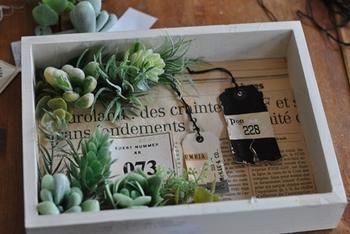 ペイントした木箱の中にオシャレな英字新聞やタグなどを張り付けます。そしてフェイクグリーンを隅に配置して、グルーガンでつけていきましょう。