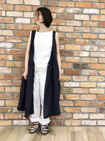ノースリーブの白トップスに、黒のロングベストをレイヤード。ノースリーブ同士のアイテムを合わせるときは、同系色でまとめるか、白×黒のように反対色で合わせると、バランスの良い着こなしができます。
