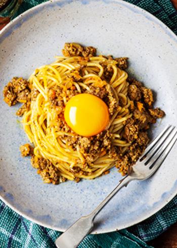 パスタのマンネリ打破に役立つ、ドライカレー×パスタの組み合わせ。カレー粉やソース、ケチャップでしっかりめに味付けしたドライカレーと、生卵をからめて満足度大の一皿に。