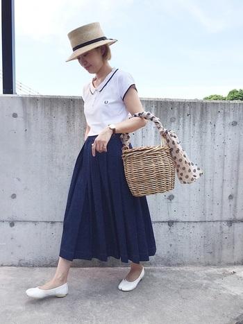 女性らしいネックデザインのポロシャツに、ボリューミーなデニムプリーツスカートを合わせた大人フェミニンな着こなし。襟のラインとボトムスのカラーをリンクさせることで、すっきり見せています。足袋デザインのフラットシューズやドット柄スカーフで、さりげなくエッジを効かせて。