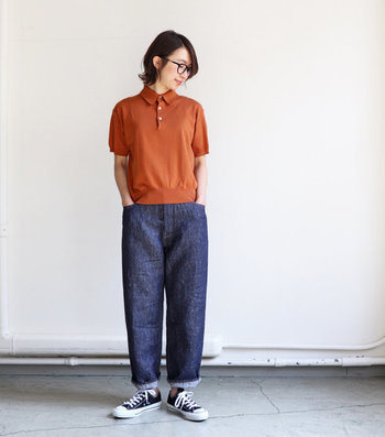 テラコッタカラーのポロシャツと濃紺デニムの組み合わせ。リネン100%の風合いとロールアップの着こなしが、ナチュラルな抜け感を演出しています。