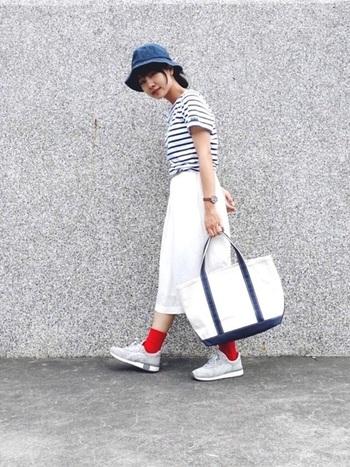ホワイト×ネイビーのキャンバスバッグとスタイリングがカラーリンクしたマリン風の着こなし。足元に赤ソックスを合わせることで、コーディネート全体でトリコカラーを表現。爽やかな夏気分を高めてくれます。