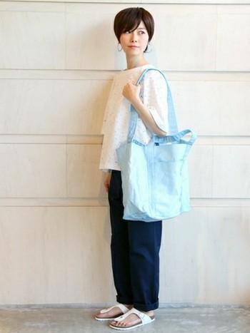 爽やかなライトブルーのキャンバスバッグが、ネイビーのパンツと相まって夏らしさを盛り上げています。特に今季は、大きめトートに注目です。