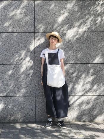 ワイドサロペットに、大きめのキャンバスショルダーをクロスボディさせた着こなし。インナーの白Tシャツと白のキャンバス地が爽やかな季節感を演出しています。