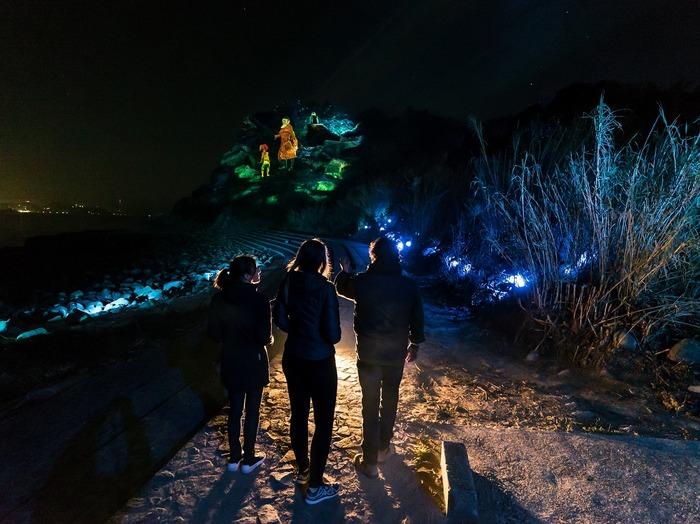 """日没後、「島⾵の湯」敷地内の専⽤バスで移動すると・・・幻想的な雰囲気あふれる森へ到着!伊王島の雄大な自然を舞台とした""""体験型マルチメディア・ナイトウォーク""""、その名も「ISLAND LUMINA(アイランド ルミナ)」の幕開けです。  プロデュースをつとめるのは、カナダを拠点に活躍する、世界最高峰のデジタルアート集団「MOMENT FACTORY(モーメントファクトリー)」。シルク・ドゥ・ソレイユの企画などを手がける彼らによって、最先端のテクノロジー技術を活用した光と映像にあふれる、約1Kmものコースが森の中に誕生しました。"""