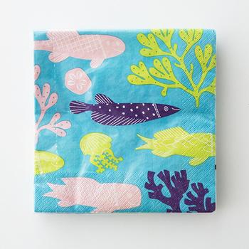 陶芸作家の鹿児島睦さんが描く魚のテキスタイルを、アートディレクターの前田景さんがパズルのように組み合わせ、ペーパーナプキン用にデザイン。