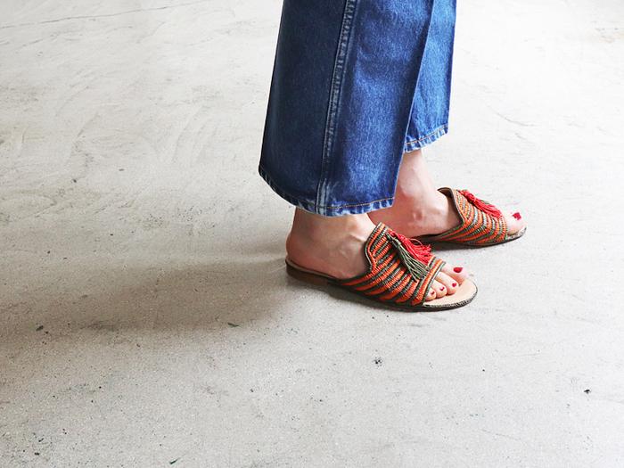 履くだけで気分が上がるような明るい配色のミュールサンダル。モロッコ・カサブランカのシューズブランド「REVE D'UN JOUR(レーヴ・ダン・ジュール)」の一足で、天然素材のラフィアを使ってハンドメイドでつくられています。オレンジとカーキのタッセルも可愛らしいアクセントに。