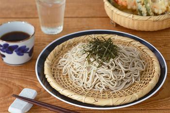 """定番の蕎麦や素麺、つけ麺やざるうどんの盛り付けにおすすめなのが""""そばざる""""。 京都の老舗「公長齋小菅」の""""そばざる""""は、丁寧に編まれた網目がとても美しいアイテム。これからの暑い季節に、この""""そばざる""""に麺を盛り付けるだけで、清涼感が生まれます。"""