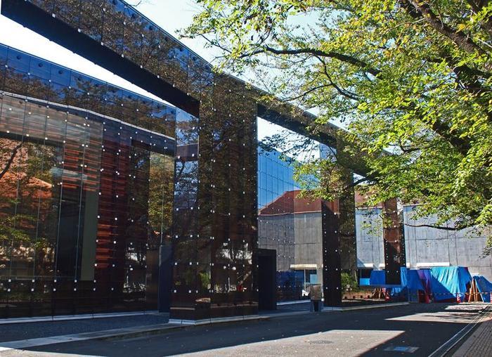 """その敷地内にある「武蔵野美術大学 美術館・図書館」は、その名の通り美術館と図書館を併設。建築家の藤本壮介氏が設計を担当し、""""書物の森""""というコンセプトのもと、渦巻き型の書架の壁をもつ図書館を生み出しました。 外観はこのように、陽の光を美しく反射する壁面ガラスが印象的です。"""