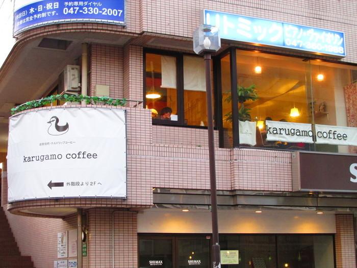 JR松戸駅西口から歩いて5分ほどのところにある「Karugamo Coffee(カルガモコーヒー)」は、交差点近くのビルの2階にあります。愛らしいカルガモのイラストが目印。